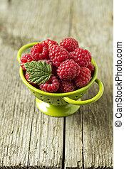 Fresh raspberries in green colander