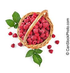 Fresh raspberries in wicker basket with green leaves