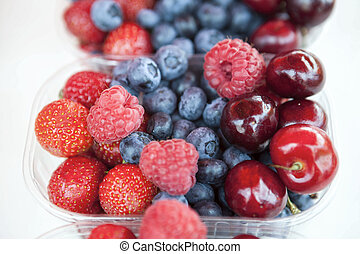Fresh , raspberries, strawberries, cherries, blueberries in the box on the market