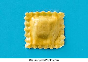 Fresh ravioli pasta on blue background. Close up