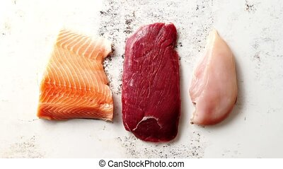 Assortment of fresh raw beef steak, chicken breast, and salmon fillet. Top view composition on white rusty background.