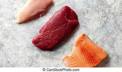 Fresh raw beef steak, chicken breast, and salmon fillet -...