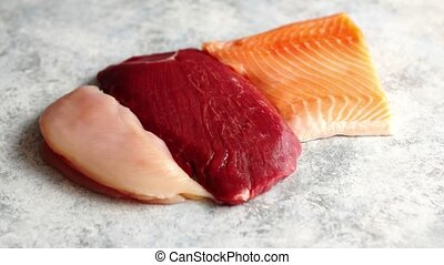 Fresh raw beef steak, chicken breast, and salmon fillet -...