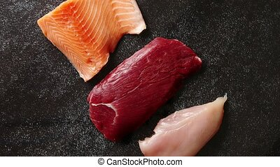 Fresh raw beef steak, chicken breast, and salmon fillet. Top...