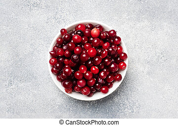 Fresh raw berries cranberries in a plate on a gray background with copy space.
