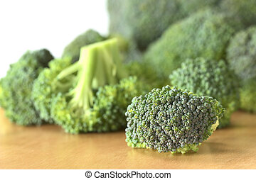 Fresh raw broccoli floret with more broccoli in the back (Selective Focus, Focus on the front of the broccoli)
