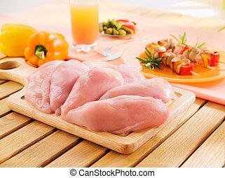 Fresh raw chicken breast arrangement on kitchen cutting board
