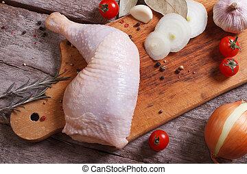Fresh raw chicken leg on a cutting board. top view