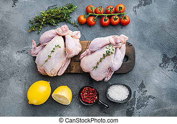 Fresh raw chicken with herbs and ingredients, on gray background, top view