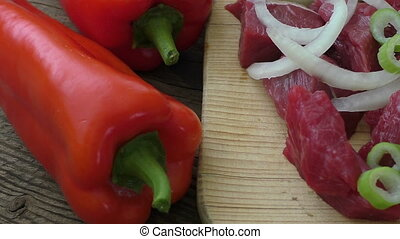 Fresh raw chopped beef on a wooden cutting board with fresh...