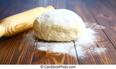 fresh raw dough with a rolling pin