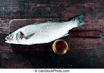 Fresh Raw Fish on Wood Board with Dish of Oil