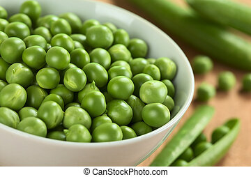 Fresh raw green pea (lat. Pisum Sativum) in white bowl...