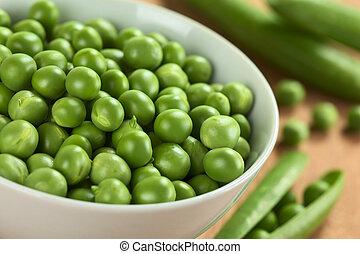 Fresh raw green pea (lat. Pisum Sativum) in white bowl...