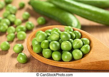 Fresh raw green pea (lat. Pisum Sativum) seeds on wooden ...