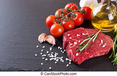 Fresh raw meat beef steak with with spices, rosemary, tomatoes and olive oil on the black slate surface.