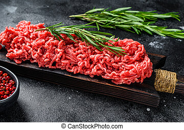 Fresh Raw mince beef, ground meat with herbs and spices. Black background. Top view