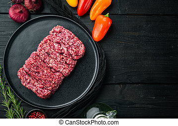 Fresh Raw mince, Minced beef, ground meat, on black wooden table background, top view flat lay with copy space for text