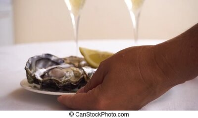 fresh raw oysters - placing a plate with oysters on table...