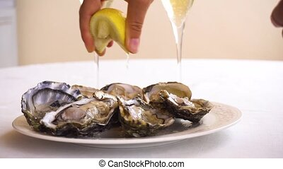 fresh raw oysters - someone hand squising lemon in plate...
