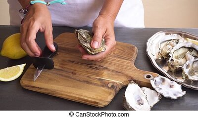 fresh raw oysters - someones hands open fresh raw oyster...