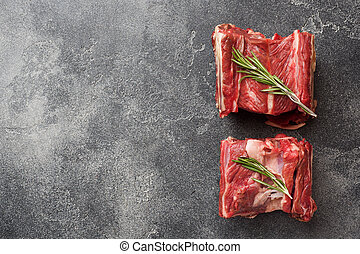 Fresh raw piece of beef rib with meat on a dark concrete background with copy space.