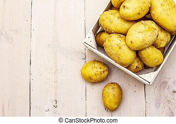 Fresh raw potatoes in wooden box