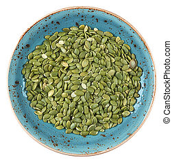 Fresh raw pumpkin seeds on a plate isolated
