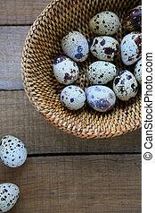 fresh raw quail eggs in a basket