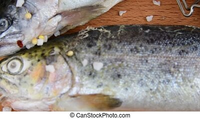 Fresh raw rainbow trouts with spices on wooden board....