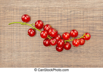 Fresh raw red currant on brown wood