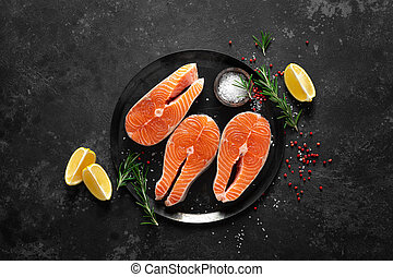 Fresh raw salmon fish steaks with cooking ingredients on ...