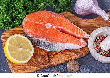 Fresh raw salmon fish steaks with fresh herbs on cutting ...