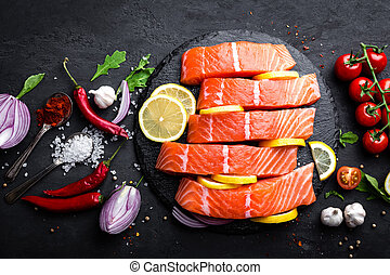 Fresh raw salmon red fish fillet on black background. Top view