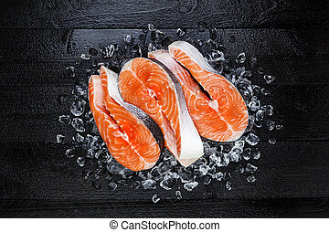 Fresh raw salmon red fish steak on ice on black wooden table top view