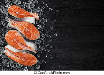 Fresh raw salmon red fish steak on ice on black wooden table top view, Fish food concept. Copy space