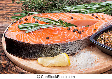Fresh raw salmon red fish steak with herbs, spices and vegetables