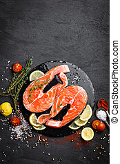 Fresh raw salmon red fish steaks on black background. Top view