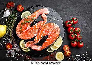 Fresh raw salmon red fish steaks on black background, top view