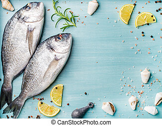 Fresh raw sea bream fish decorated with lemon slices, herbs and shells on blue wooden background, copy space