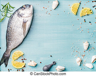 Fresh raw sea bream fish decorated with lemon slices, spices and shells on blue wooden background, copy space