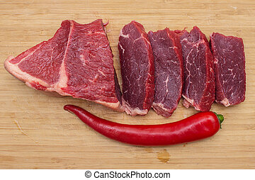 Fresh raw sliced meat beef on an wooden cutting board.