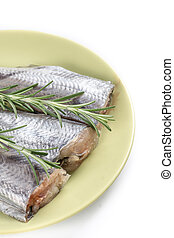 Fresh raw slices of hake fish with rosemary branches on the plate with copy space