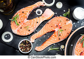 Fresh raw unprepared fish salmon or trout, steaks, in a skillet for cooking, with salt, pepper On black stone concrete table, copy space top view