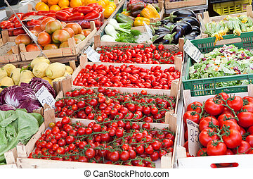 Fresh raw vegetables in wooden boxes at open street market -...