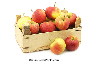 Fresh red and yellow apples in a wooden crate