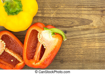 Fresh red and yellow bell peppers, on wooden surface