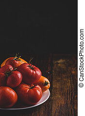 Fresh red and yellow tomatoes on plate
