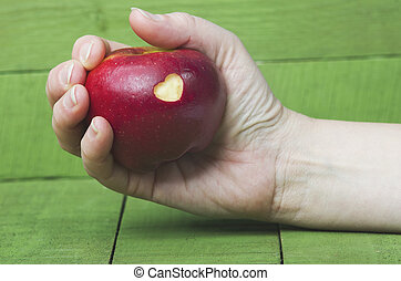 Fresh red apple with a heart shaped cut-out in woman hand on wood table. Protect your heart