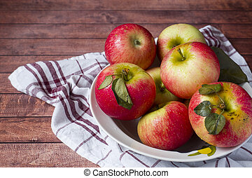 Fresh red apples with green leaves in a plate on a napkin. Dark wooden background.